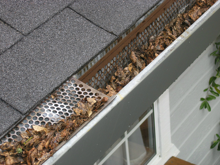 Guttering on a house with gutter guard and autumn leaves