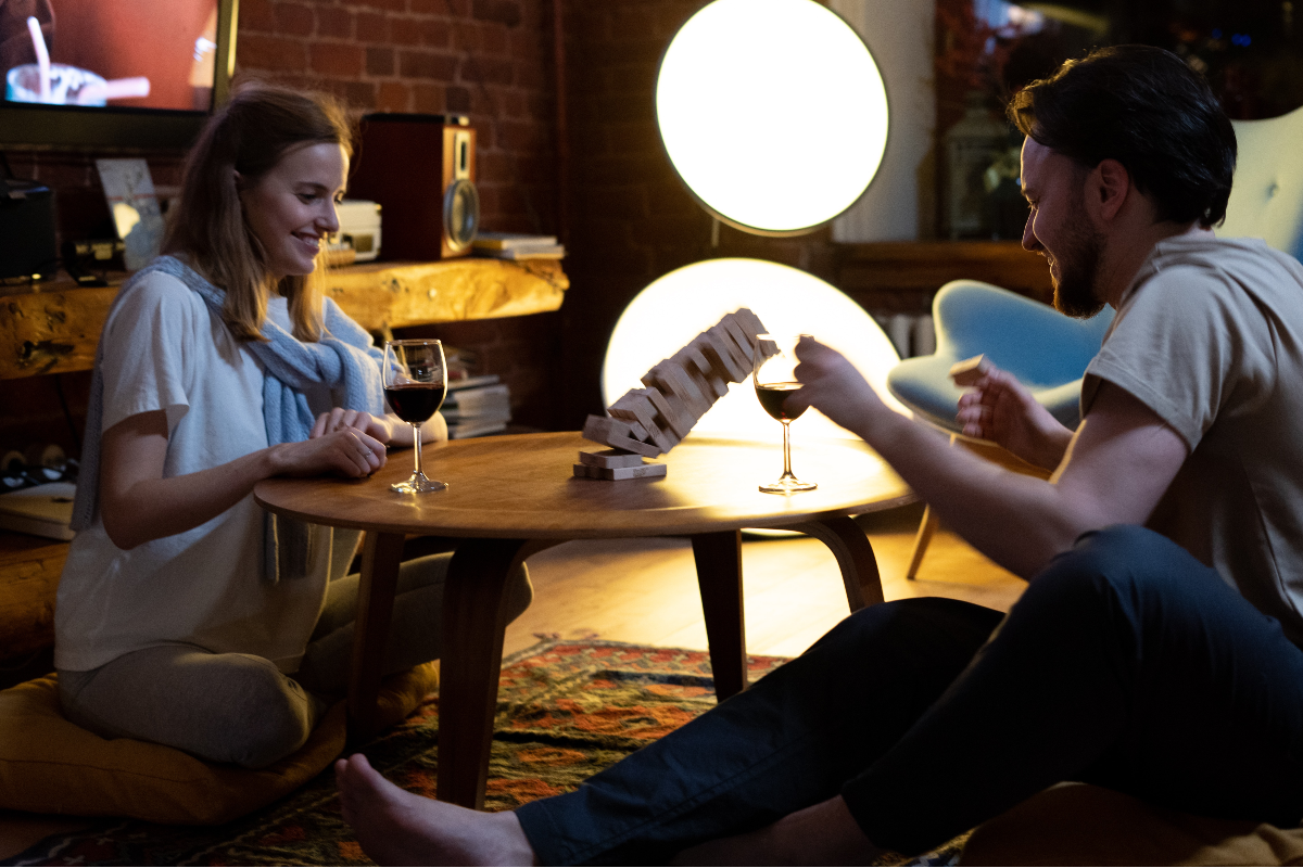 Couple playing Jenga whilst drinking wine